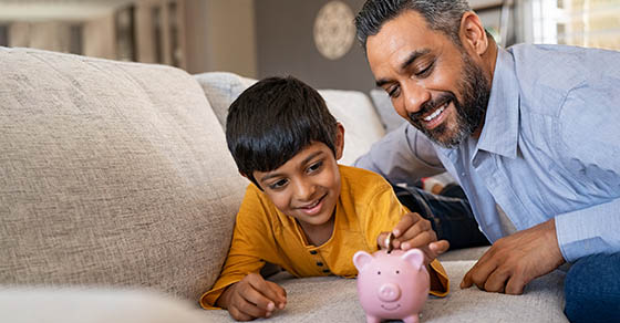 Happy indian son saving money in piggy bank with father. Lovely ethnic father teaching to little boy importance of saving money for future. Smiling middle eastern kid adding coin in piggybank while lying on couch with dad at home.