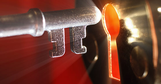 silver key being inserted into gold keyhole with light shining through it