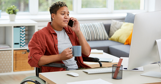 person in wheelchair at home desk holding coffee cup while on phone call in front of computer