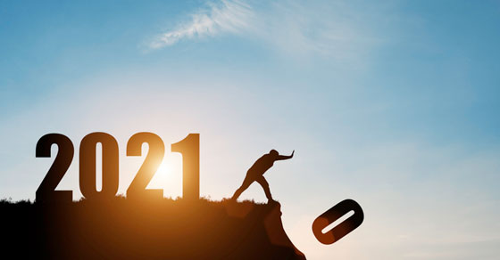 silhouette of 2021 on a cliff with person pushing zero off edge turning 2020 into 2021