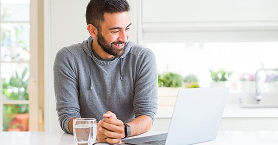 Man sitting at kitchen table smiling at open laptop