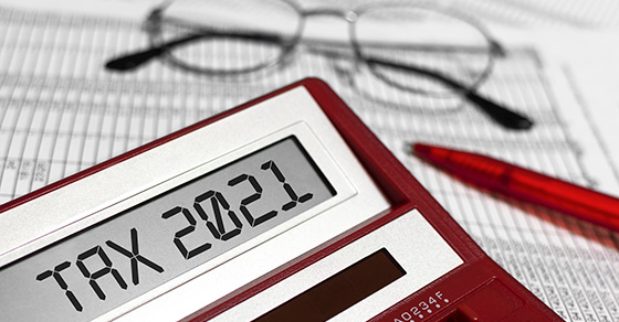 Calculator with TAX 2021 on screen and glasses in background