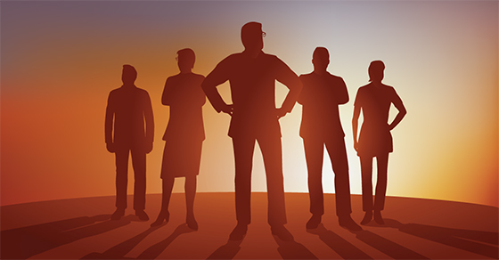 silhouette of 5 business people in V formation looking toward bright horizon