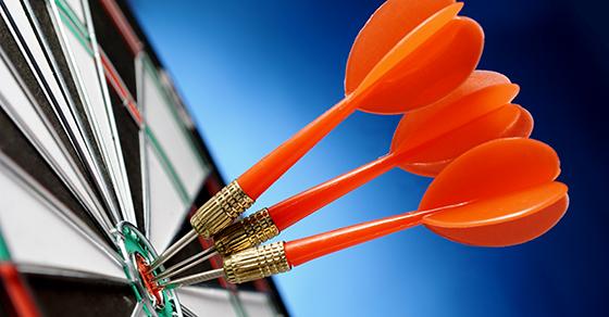 close up of 3 darts on dartboard bullseye