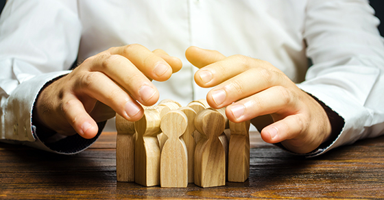 close up of hands over a group of wooden figures representing employees as if protecting them