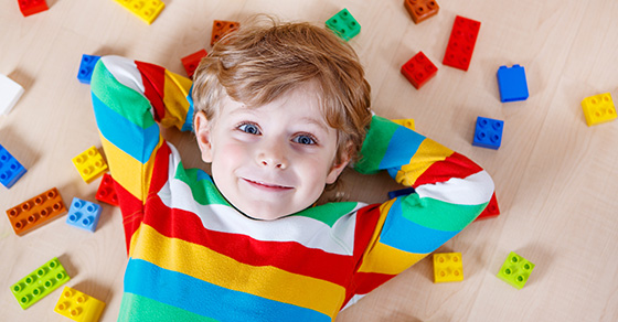close up of young child laying on floor with building blocks scattered around
