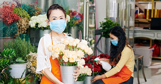 workers at florist. One female worker watering plants in background while woman holds pot of cut roses in foreground