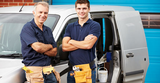 Father and son wearing tool belts leaning against work vehicle smiling with arms crossed