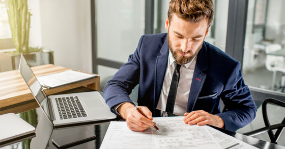 business man at desk looking over papers with laptop open to his side.