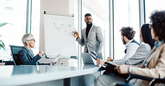 four business people sitting around conference room table while businessman is at easel drawing charts