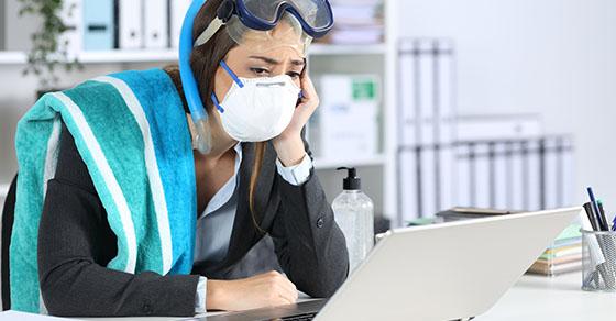 Sad executive wearing mask watching laptop at office with canceled vacation due coronavirus