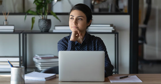 woman sitting at laptop looking thoughtfully into the distance