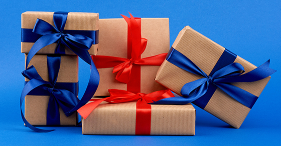 stack of 5 gift-wrapped boxes, three with blue ribbons and bows and two with red ribbons and bows