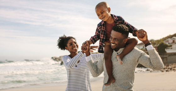 smiling and laughing family walking on beach with son riding on shoulders of dad while mom helping hold him steady