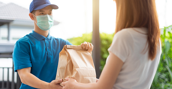 Gig economy delivery person wearing mask handing bag to customer at their door