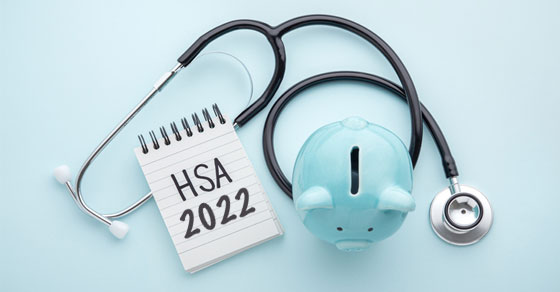 blue piggy bank with stethoscope and small notebook that says HSA 2022 on a light blue background