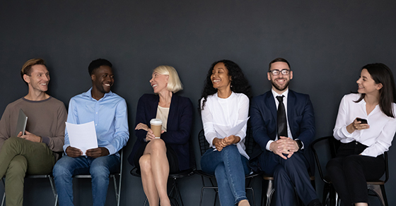 group of six diverse individuals sitting in chairs laughing and smiling at each other.