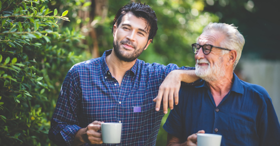 Father and son standing next to each other holding coffee cups.  Son is resting his arm on father's shoulder while father looks up at son smiling