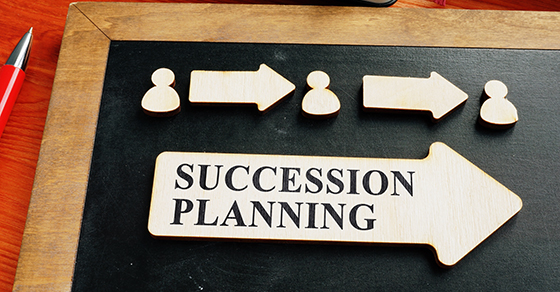 blackboard with wooden cutouts on it.  Cutouts are person profile, arrow, person profile, arrow, person profile, large arrow that says succession planning on it.