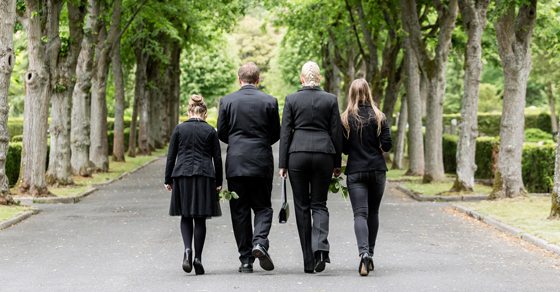 grieving family wearing black walking down road