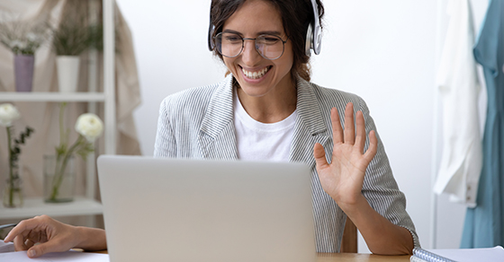 woman at computer with headset.  She is smiling and waving to screen as if to greet a virtual meeting participant