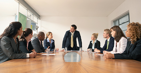 9 business people around a large conference table.  4 people are seated on opposite sides of the table from each other while another stands at the head of the table leading the meeting.  This person is leaning on the table being supported by their hands as if making a point.