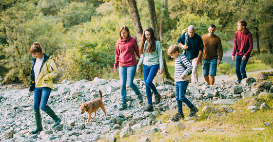 family of 7 individuals (multi-generational) hiking with dog along riverbed
