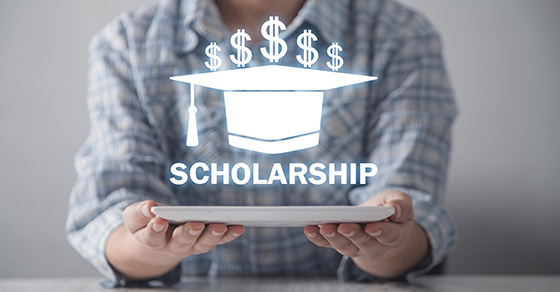 close up of upper torso of person holding a plate out in front of them with both hands.  Hovering over the plate is a graduation cap with 5 dollar signs on the top of it and the word scholarship below it.