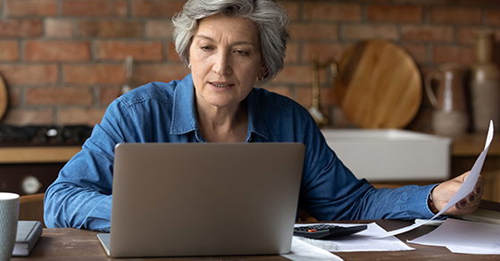 woman sitting in front of laptop with papers in hand and on desk.  A calculator is sitting on the paper on the desk